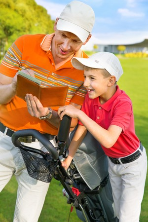 Father with son are counting points of game at golf course Stock Photo