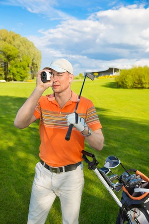 man golfer watching into rangefinder at his hit