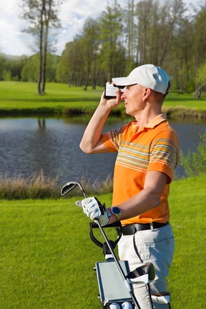 rangefinder: man golfer watching into rangefinder at his hit