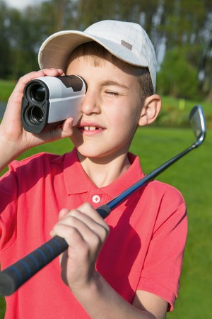 rangefinder: 9 year boy golfer watching into rangefinder at his hit