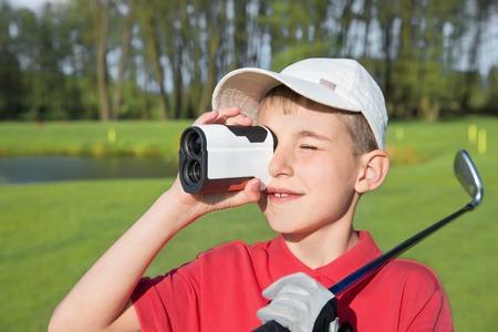9 year boy golfer watching into rangefinder at his hit