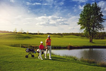 Father with son are walking at golf field Stock Photo