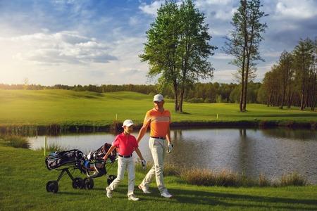 Vader met zoon lopen op golfgebied Stockfoto