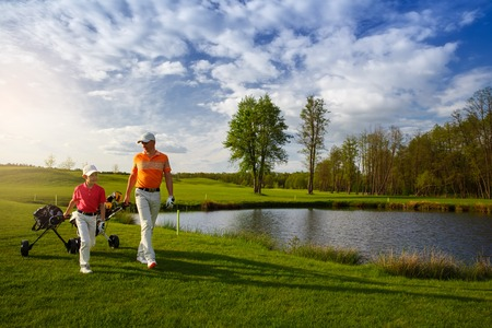 golf bag: Father with son are walking at golf field Stock Photo