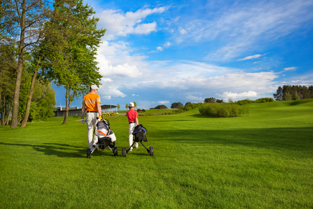 parent child: Father with son are walking at golf field Stock Photo