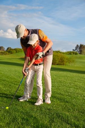 Padre con el hijo están entrenando en el campo de golf Foto de archivo
