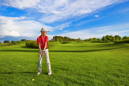 Boy golf player hitting by iron from fairway