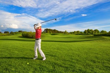 Boy golf speler raakt door ijzer van fairway Stockfoto