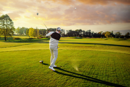 Professional male golf player hitting by driver from tee Foto de archivo