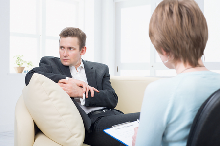 dipsomania: Upset man with a problem on a reception for a psychologist