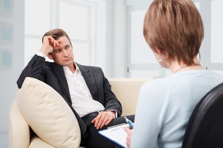 Oppressed man with a problem on a reception for a psychologist