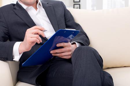 terapia psicologica: estar listo psic�logo macho para tomar notas sentados en el sof�