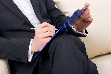 male psychologist  being ready to take notes  sitting on the couch Stock Photo