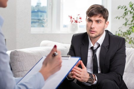 social worker: Depressed businesman with a problem on a reception for a psychologist
