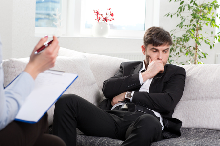 terapia psicologica: Depressed businesman with a problem on a reception for a psychologist