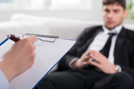 terapia psicologica: Sobre la opini�n del hombro, de un hombre de negocios se sientan en un sof� hablando con su psiquiatra
