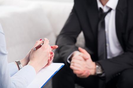 Sobre la opinión del hombro, de un hombre de negocios se sientan en un sofá hablando con su psiquiatra