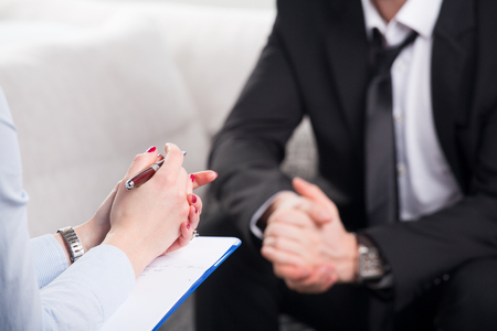 obra social: Sobre la opinión del hombro, de un hombre de negocios se sientan en un sofá hablando con su psiquiatra