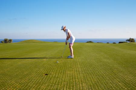 teen golf: jugador de golf femenino joven que juega en curso verde