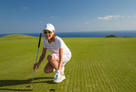 teen golf: young female golf player is putting off a ball from hole