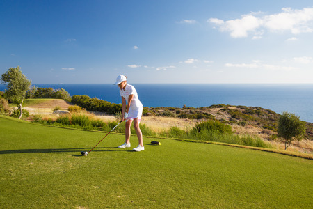 young female golf player playing on green course