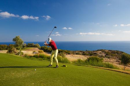 Jugador profesional de golf masculino golpear por el conductor desde el tee Foto de archivo