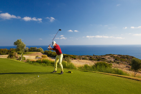 Professional male golf player hitting by driver from tee Stockfoto
