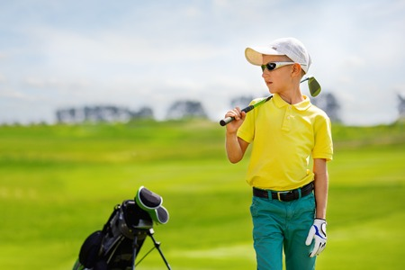 Portrait of boy golfer in golf course at summer day