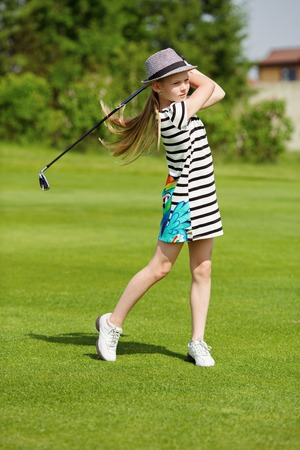 Girl golf player practicing in golf school Standard-Bild