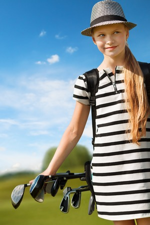 10 years girls: Girl golf player walking on golf course with club bag