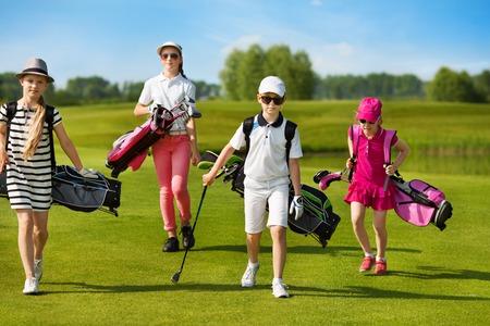 Kinderen lopen op fairway met zakken op golfschool Stockfoto