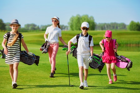 ir al colegio: Niños caminando en espacio abierto con bolsas en la escuela de golf