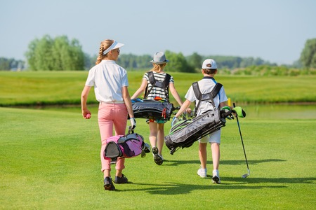 Kids walking on fairway with bags at golf school, back view