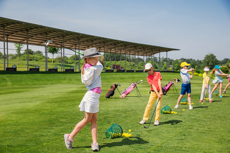 Kids warming up at golf school at summer day Stock Photo