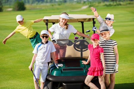 Children posing near golf car at golf course at summer day