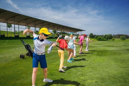 Niños calentamiento en la escuela de golf en día de verano Foto de archivo - 54177658
