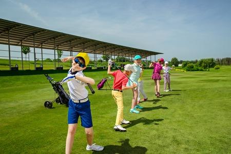 Niños calentamiento en la escuela de golf en día de verano Foto de archivo - 54177756