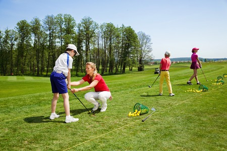Kids practicing hits at golf school at summer day Standard-Bild