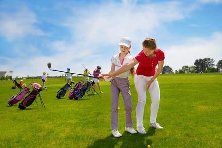 Los niños que practican golpes con instructor en la escuela de golf en día de verano Foto de archivo - 61145956