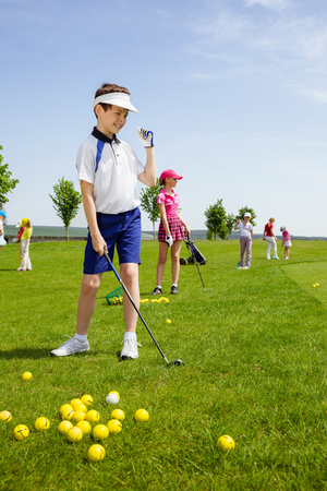 Happy boy golf player practicing in golf school Standard-Bild