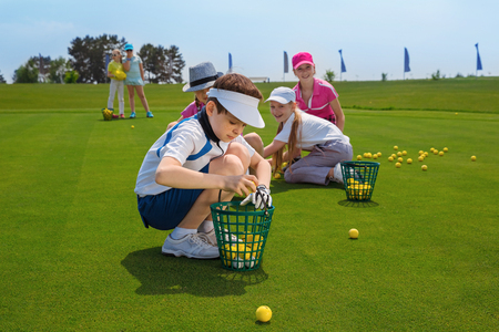 Kids putting balls into basket at golf course