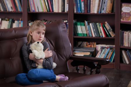 petite fille triste: D�prim� seule pleurer fille assise avec des jouets � la salle Banque d'images
