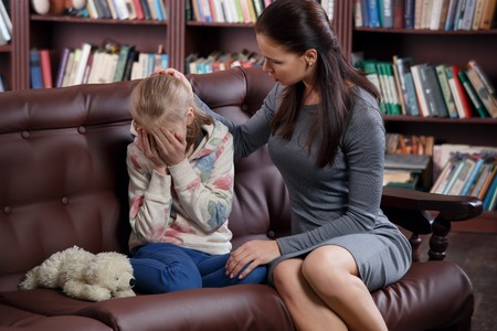 Child psychologist with a little girl, a child is crying