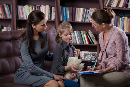 alabanza: Joven madre con su hija en la consulta psic�logo Foto de archivo