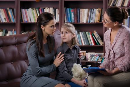 Joven madre con su hija en la consulta psicólogo Foto de archivo