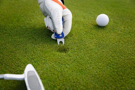 Male hand in glove marking ball position on the green. Focus on  pitchmark