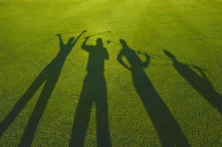 Four golfers with open hands silhouette on grass Standard-Bild