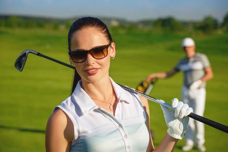 Portret van jonge sportieve vrouwen golfspeler golfen met de man op zonnige dag