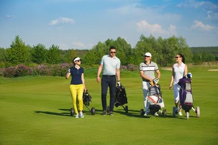 화창한 날에 골프 코스를 걷고있는 4 명의 친구 골퍼 스톡 콘텐츠