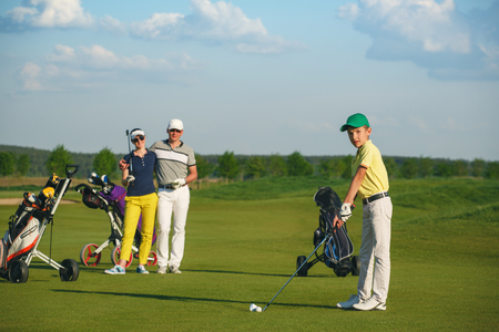 Boy golfer with parents plaing golf at sunny day